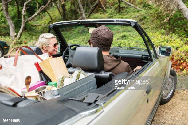 Couple with food and drink travelling in convertible