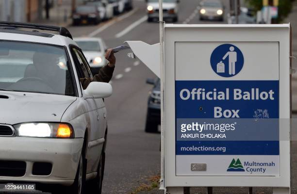 Oregon residents drop off their ballots near the Multnomah County Elections building in Portland, Oregon, on November 3, 2020. - Americans were...