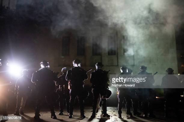 """Oregon State Police and Salem Police guard the Oregon State Capitol building during dueling Black Lives Matter and """"Stop the Steal"""" protests on..."""