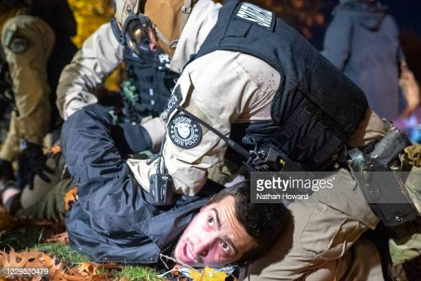 "Oregon State Police arrest a Black Lives Matter protester during a dueling rally with a ""Stop the Steal"" rally on November 7, 2020 in Salem, Oregon...."