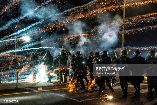 Oregon State Troopers and Portland police advance through tear gas and fire works while dispersing a protest against police brutality and racial...