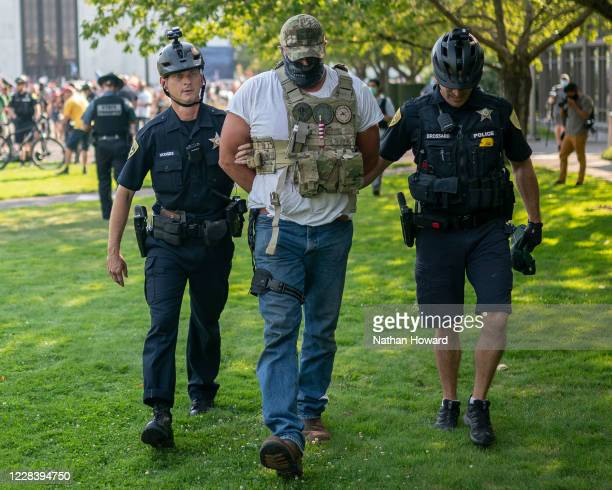 Oregon State Troopers and Salem police arrest a far-right protester following a clash with counter protesters on September 7, 2020 in Portland,...
