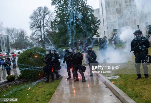 Oregon State Troopers react as a firework explodes near them during a protest on January 6, 2021 in Salem, Oregon. Trump supporters gathered at state...
