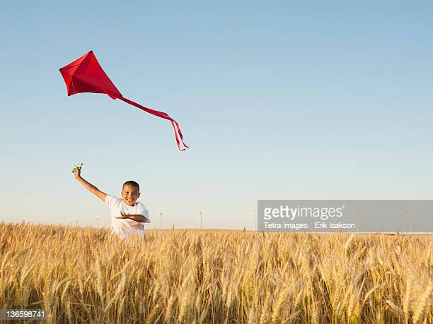 USA, Oregon, Wasco, Boy (10-11) playing with kite in wheat field