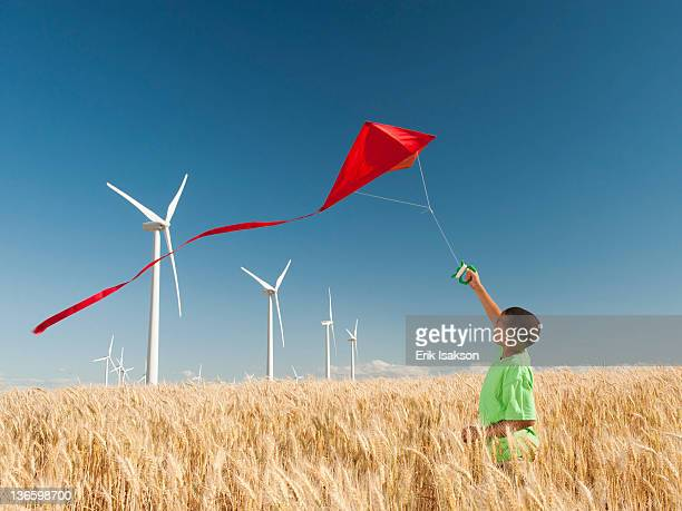 usa, oregon, wasco, boy (8-9) playing with kite in wheat field, wind turbines in background - kite toy stock pictures, royalty-free photos & images