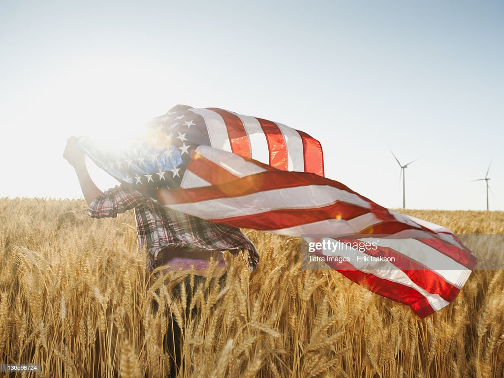 USA, Oregon, Wasco, Girl (12-13) flying american flag in wheat field : Stock-Foto