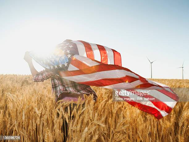 USA, Oregon, Wasco, Girl (12-13) flying american flag in wheat field