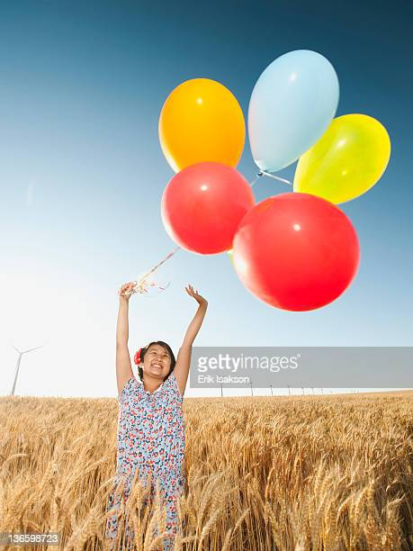 USA, Oregon, Wasco, Happy girl (10-11) standing with balloons in wheat field