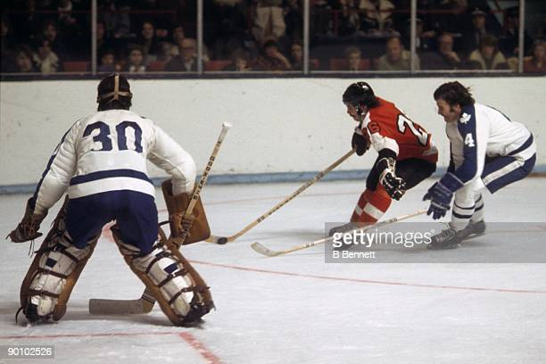 Orest Kindrachuk of the Philadelphia Flyers skates with the puck against Dunc Wilson and Mike Pelyk of the Toronto Maple Leafs during a game in the...