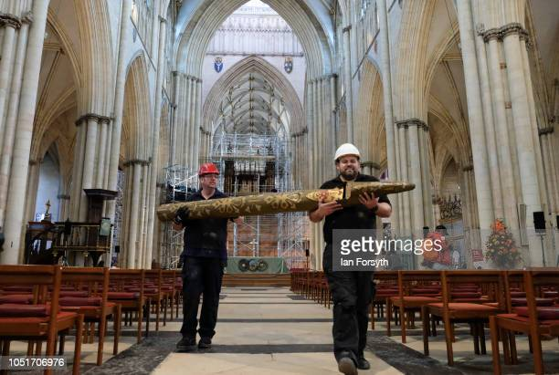 Organ restoration specialists pose for pictures with one of the organ pipes as work begins to refurbish York Minster's Grand Organ for the first time...
