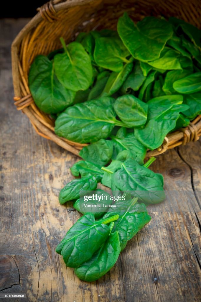 Organic baby spinach in a basket and in front of it : Stock-Foto