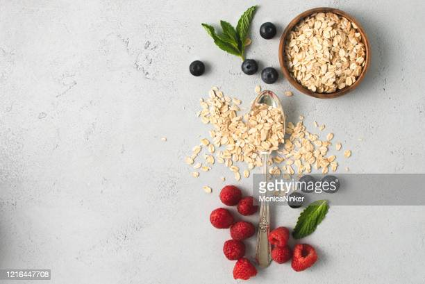 organic berries, oatmeal and minte leaves in contemporary composition - cereale foto e immagini stock
