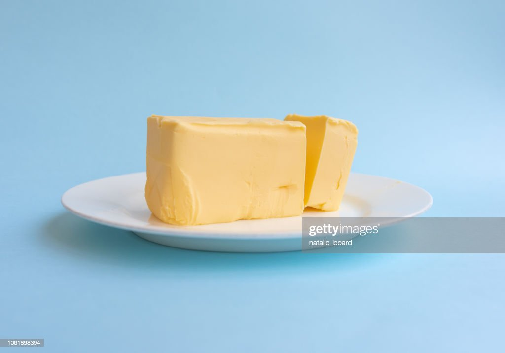 Organic butter on white plate against blue background : Stock Photo