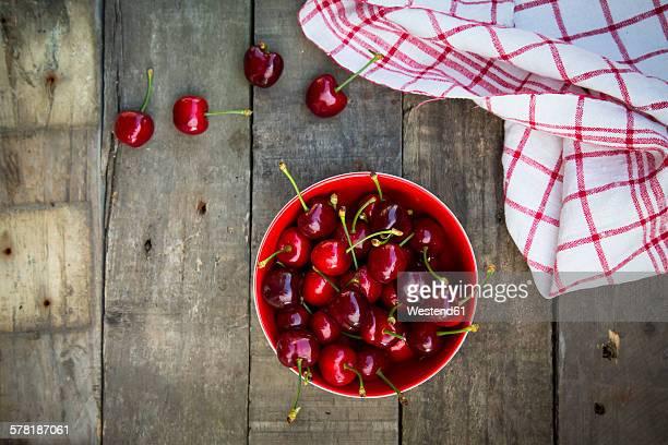 organic cherries in bowl, kitchen towel on wood - kirsche stock-fotos und bilder