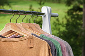 Organic clothes, t-shirts hanging on wooden hangers with green forest, nature in background.