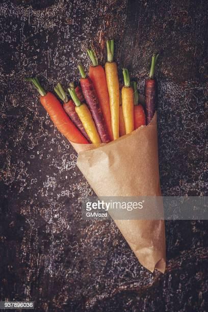 bio-farbigen karotten auf rustikalen hintergrund - vegetarisches gericht stock-fotos und bilder