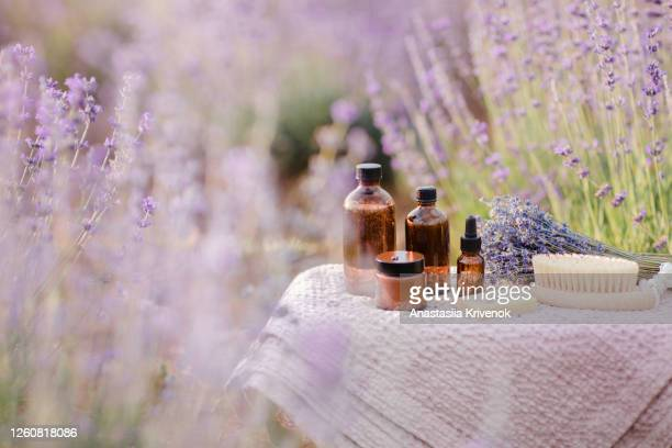 organic cosmetics bottles, essential oil and soap in lavender field in the summer. aromatherapy. skincare concept. - france stock pictures, royalty-free photos & images