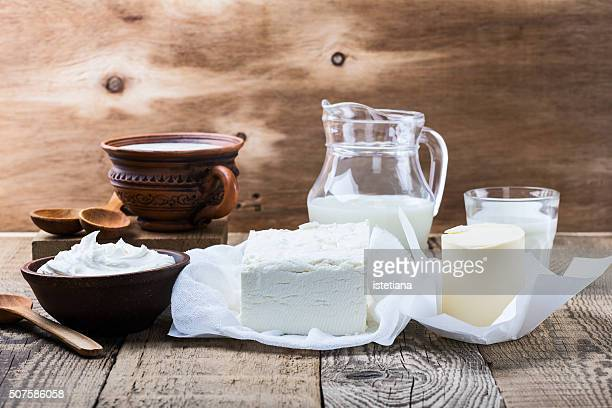 Organic dairy products: milk, yogurt, cream, cottage cheese, butter on a wooden background in rustic style
