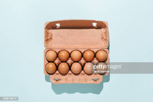 organic eggs in cartons tray on blue background. flat lay, top view - organic stock pictures, royalty-free photos & images