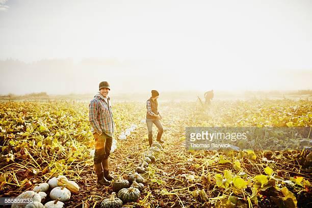 Organic farm owner standing next to organic squash