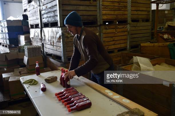 Organic farm worker Lee Griffin packs bottles of Raspberry Compote made from raspberrys from the fields of Brambletye Fruit Farm East Sussex which is...