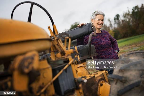 Bio-Bauernhof bei der Arbeit. Eine Frau mit einem Traktor.