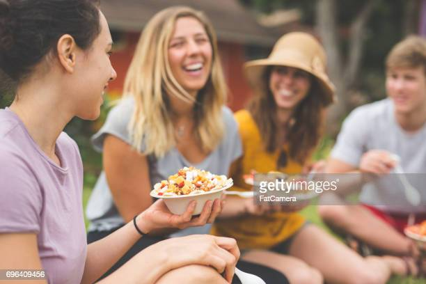 organic fruit stand - owner eating and enjoying selection of organic fruit together with friends - good posture stock pictures, royalty-free photos & images