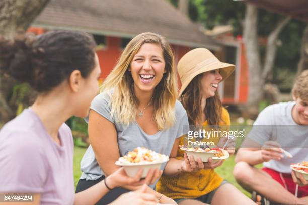 Organic Fruit Stand - Owner eating and enjoying selection of organic fruit together with friends
