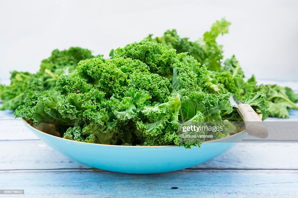 Organic kale in a blue bowl on wood : Stock-Foto