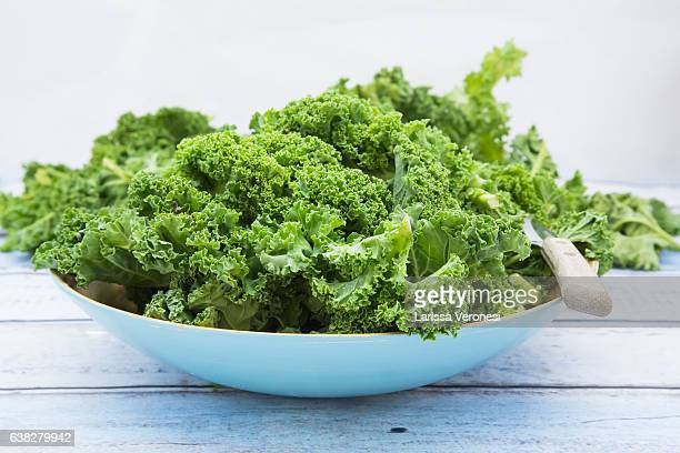 organic kale in a blue bowl on wood - kale stock photos and pictures