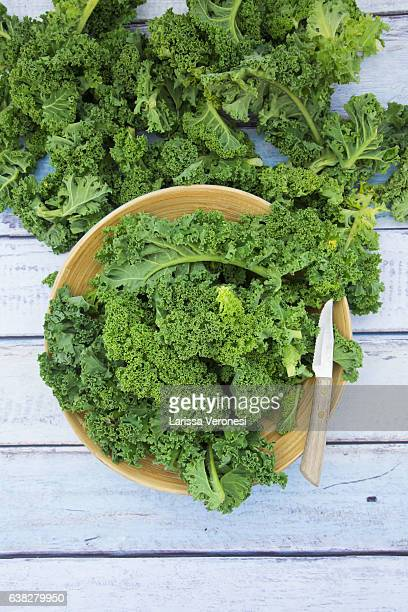 Organic kale in a blue bowl on wood