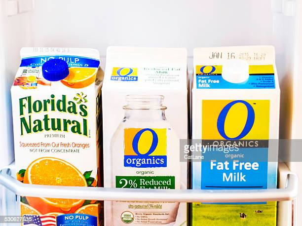 organic milk and orange juice in refrigerator - juice carton stock photos and pictures