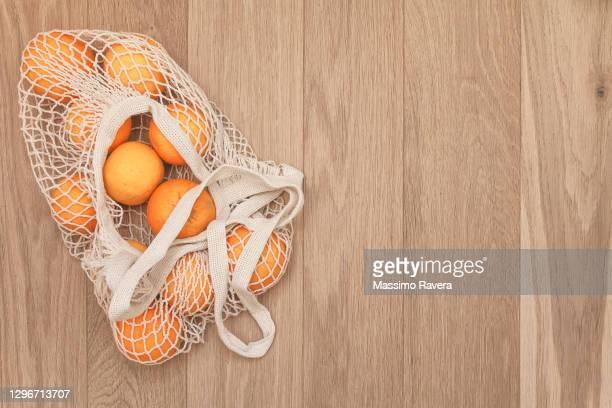organic oranges on wood - malla textil fotografías e imágenes de stock