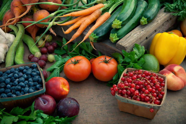 organic produce pile on a brown table - vegetables stock pictures, royalty-free photos & images