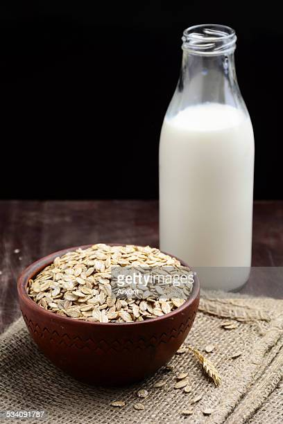 organic rolled oats in bowl and bottle of milk - rolled oats stock photos and pictures