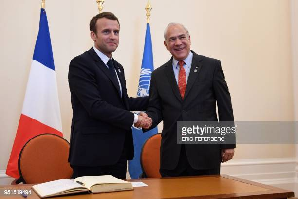 Organisation for Economic Co-operation and Development Secretary-General Angel Gurria shakes hands with French President Emmanuel Macron during the...