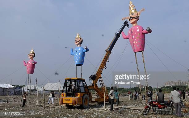 Organisers erecting effigy of demon king Ravana with the help of crane ahead of Dussehra festival on October 12 2013 in Noida India The effigies are...