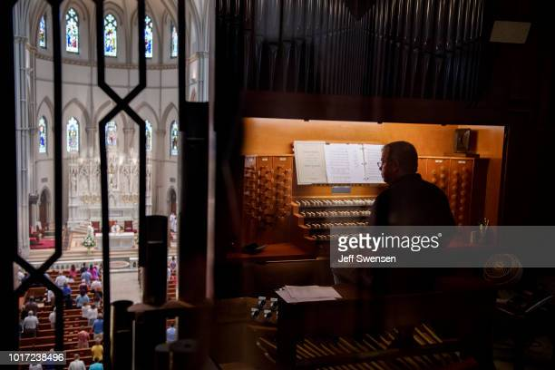 Organist Don Fellows is reflected on a glass encasement as parishioners worship during a mass to celebrate the Assumption of the Blessed Virgin Mary...