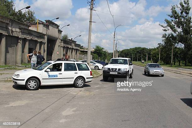 Organization for Security and Cooperation in Europe observers' car is seen as the bodies of MH17 crash victims arrive Manlisova military tanks and...