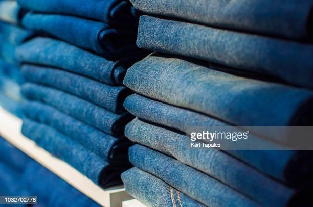 organized blue denim pants on a shelf - jeans stock-fotos und bilder