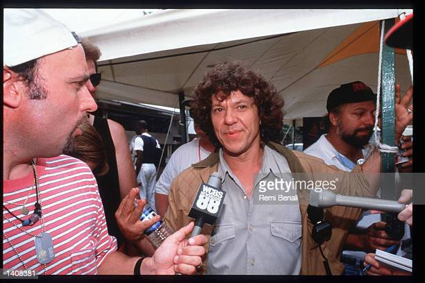 Organizer Michael Lang speaks to journalists at the Woodstock 25th anniversary concert August 13 1994 at Winston Farm in Saugerties NY An...