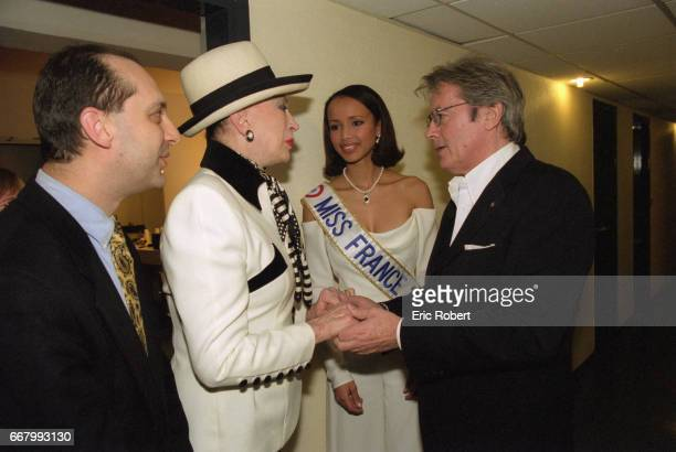 Organizer of the Miss France pageant Genevieve de Fontenay and actor Alain Delon greet each other as Sonia Rolland Miss France 2000 looks on
