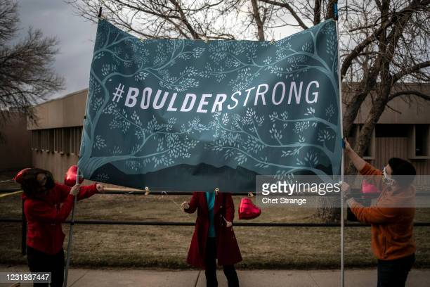 Organizers erect a #BoulderStrong banner before a vigil to commemorate the victims of a mass shooting at a King Soopers grocery store on Thursday,...