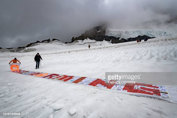 Organizers rollout a long roll made up of more than 2500 laminated postcards put together to make up a message against climate change during a test...