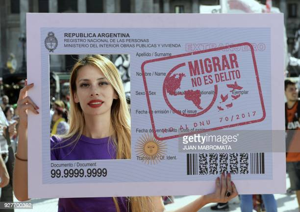 Oriana Bobadilla of Chilean descent poses holding an Argentine ID banner reading in spanish 'Migrate is not a crime' during a protest in front of the...