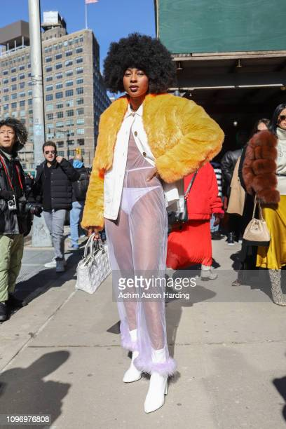 Oriane Adjibi is seen wearing an orange faux fur jacket by DOlls Kill a Savage jumpsuit white Public Desire shoes and a white Dior bag on the street...