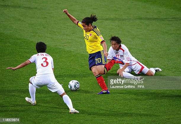 Orianica Velasquez of Colombia skips past Jon Myong Hwa and Ho Un Byol of Korea DPR during the FIFA Women's World Cup 2011 match between Korea DPR...