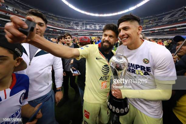 Oribe Peralta and Edson Alvarez of America celebrate with the championship trophy after the final second leg match between Cruz Azul and America as...