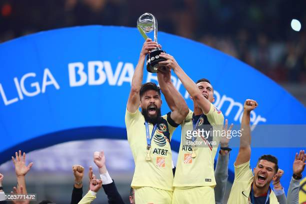 Oribe Peralta and Paul Aguilar of America hold up the championship trophy after winning the final second leg match between Cruz Azul and America as...