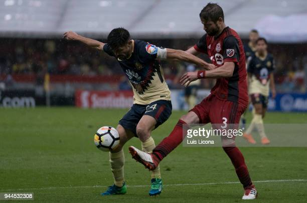 Oribe Peralta of America and Drew Moor of Toronto fight for the ball during the semifinal second leg match between America and Toronto at Azteca...
